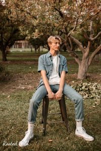 fashion photography pose of man sitting with hands on stool